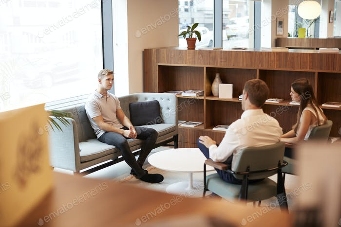 Businessman And Businesswoman Interviewing Male Candidate In Office