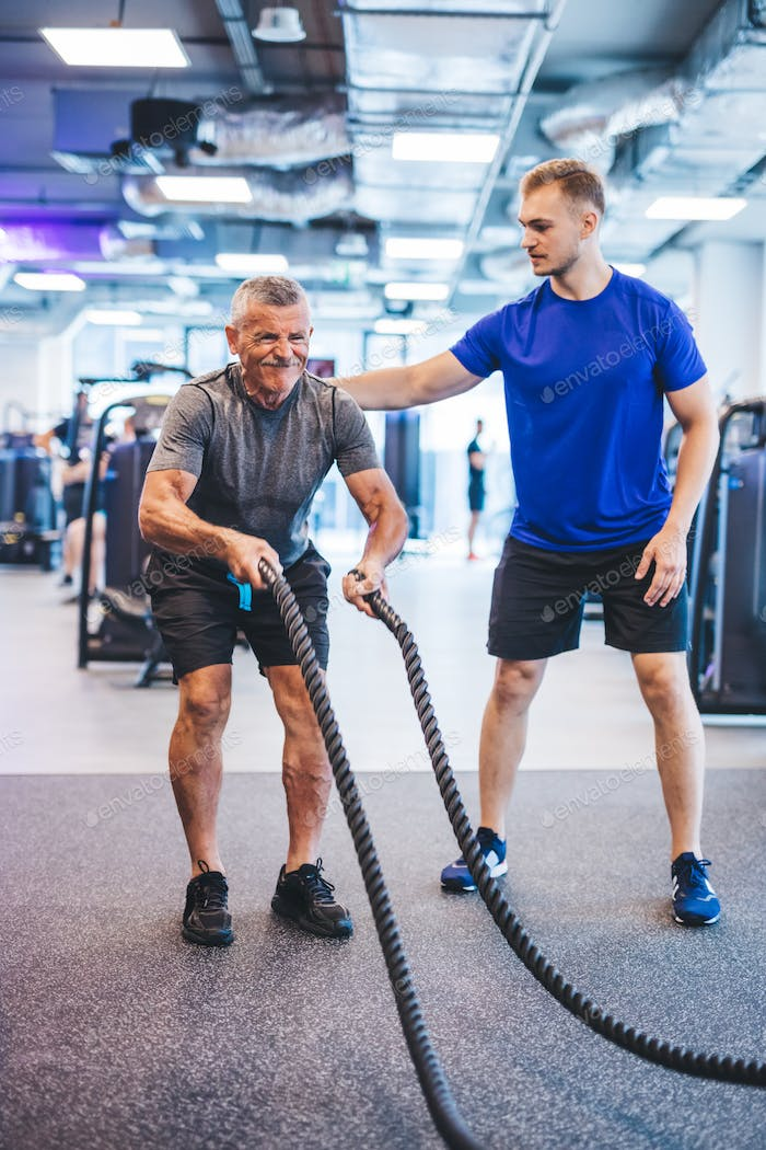 Senior man exercising at the gym with gym instructor.