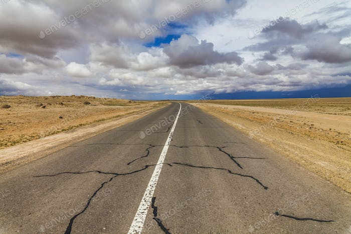 Lonely road in the desert under a cloudy sky