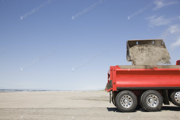54657,Truck shoveling sand on beach