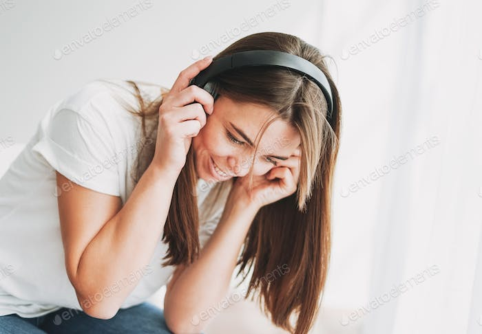 Young woman with freckles listening music by headphones