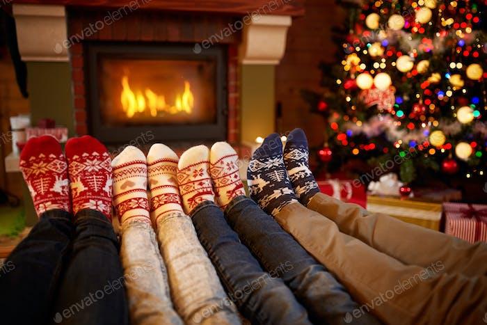 Feet in wool socks near fireplace in Christmas time