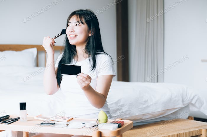 Young Asian woman doing makeup at home