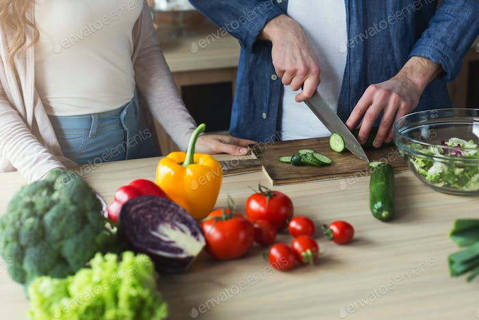 Closeup of couple cooking healthy food together
