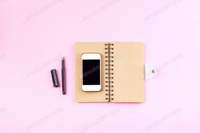 Notebooks craft, pen and smart phone on a pastel pink background . Mockup concept