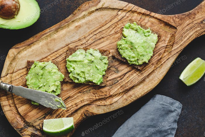 Three snacks with rye bread and mashed avocado. The concept of healthy fast snack.