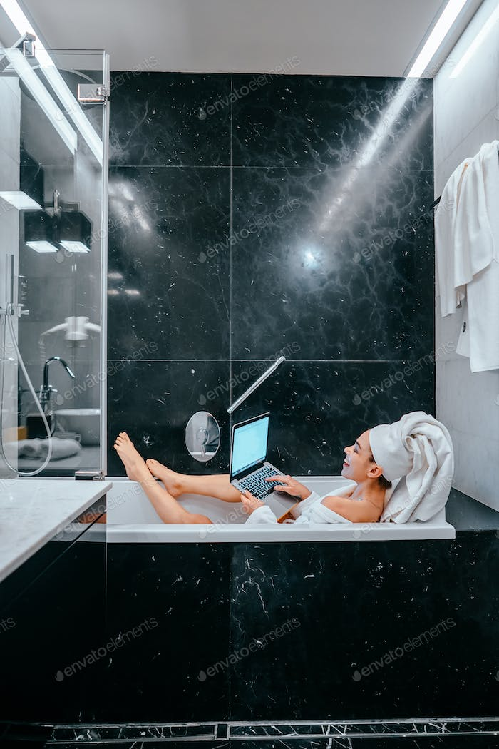 Relaxed woman with towel on hair lying in bathtub