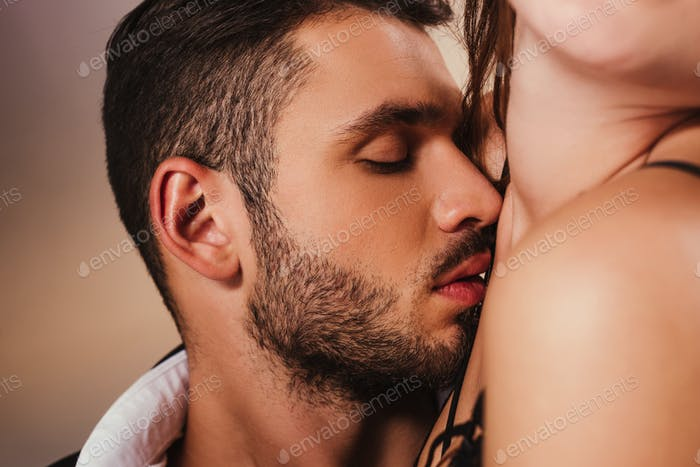 sensual handsome man cuddling to young woman