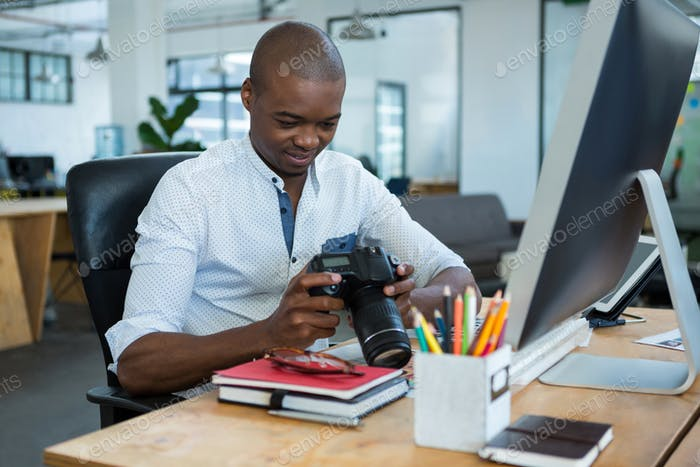 Male graphic designer reviewing captured images in his digital camera at desk