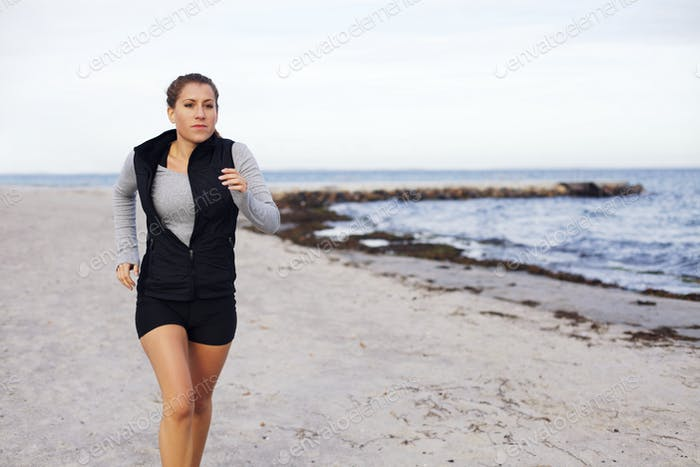 Healthy young female jogging on beach