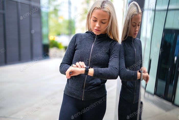 Woman using fitness smart watch device before running in city