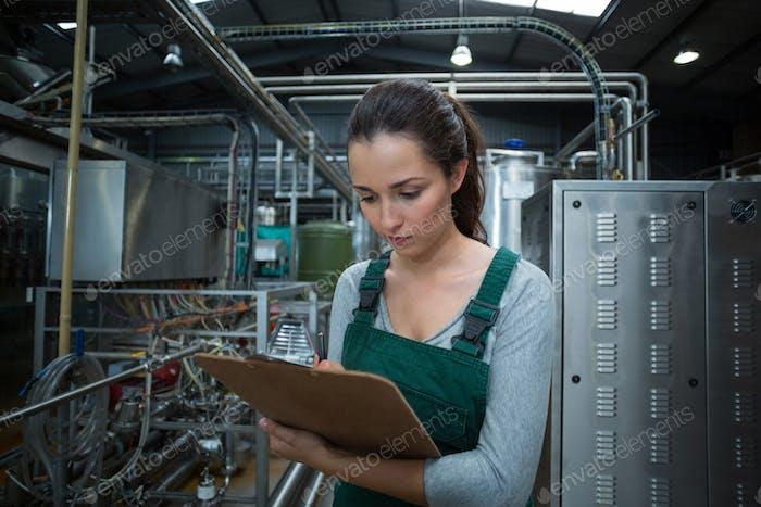 Thumbnail for Weibliche Fabrikarbeiter pflegen Rekord auf Zwischenablage in der Fabrik