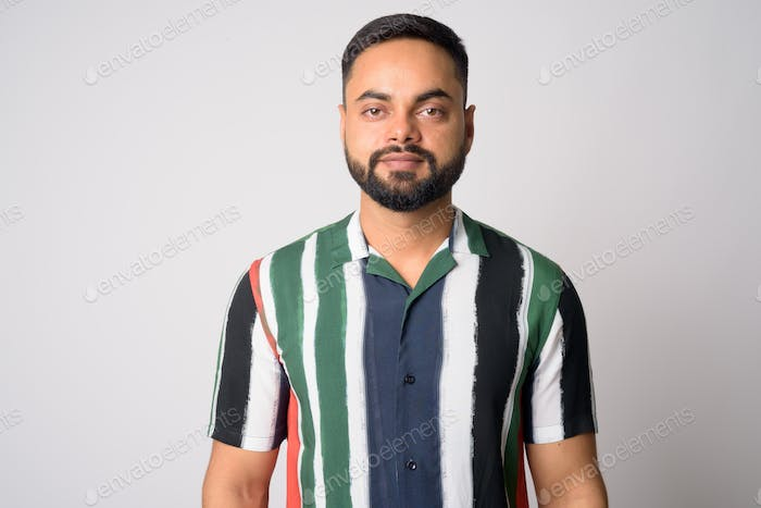 Face of young handsome bearded Indian man