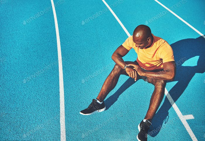 Young athlete sitting on a track checking his lap time
