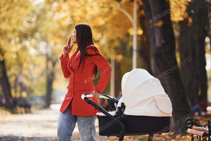 Mother in red coat have a walk with her kid in the pram in the park at autumn time and smoking