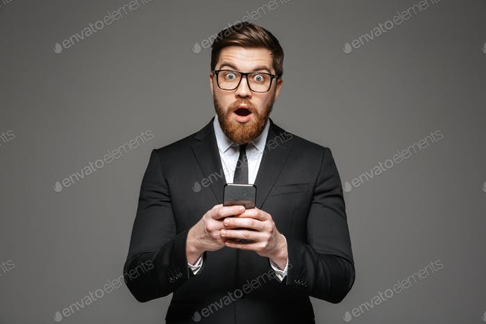 Portrait of an excited young businessman dressed in suit