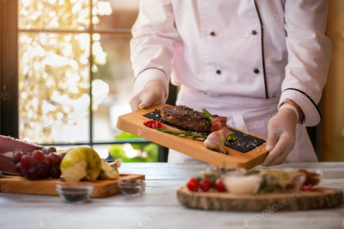Cook holds board with meat