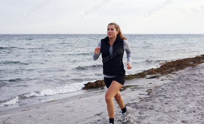 Healthy young woman jogging at the beach