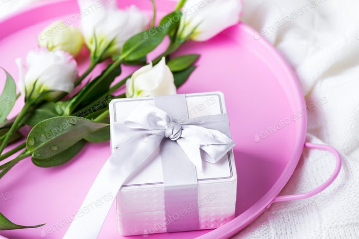 Gift box and pastel flowers eustoma for Valentines or Mothers day on pink tray on bed . Flat lay