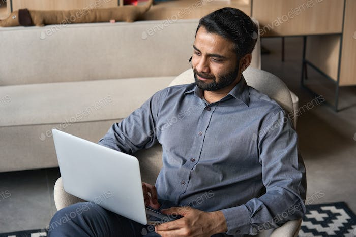 Serious indian businessman working on laptop computer from home office.