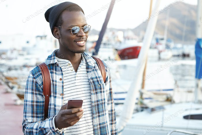 Travel, tourism, communication, technology and people concept. Handsome black man with backpack wear