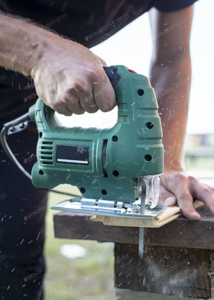 Man cuts wood products, using electric jigsaw