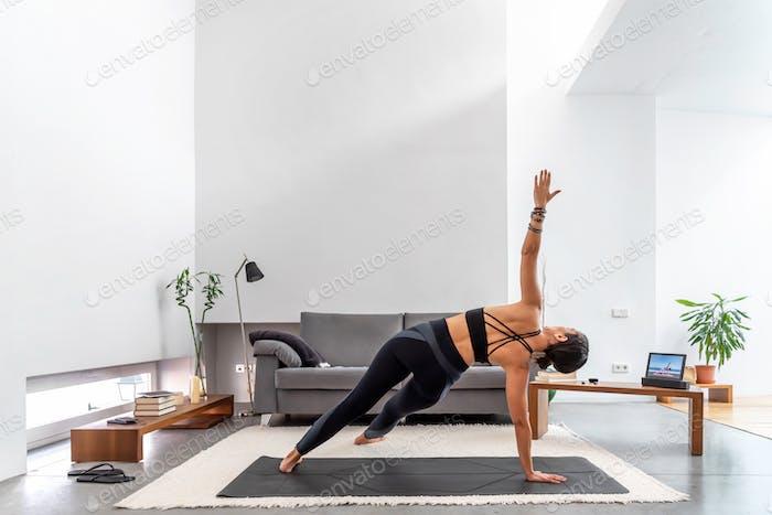 Fit Frau praktiziert Yoga auf ihrer Matte mit einem Online-Trainingsprogramm in ihrem Tablet