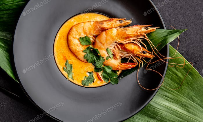 Seafood Soup decorated with whole shrimps and tropical leaves on black plate, black background