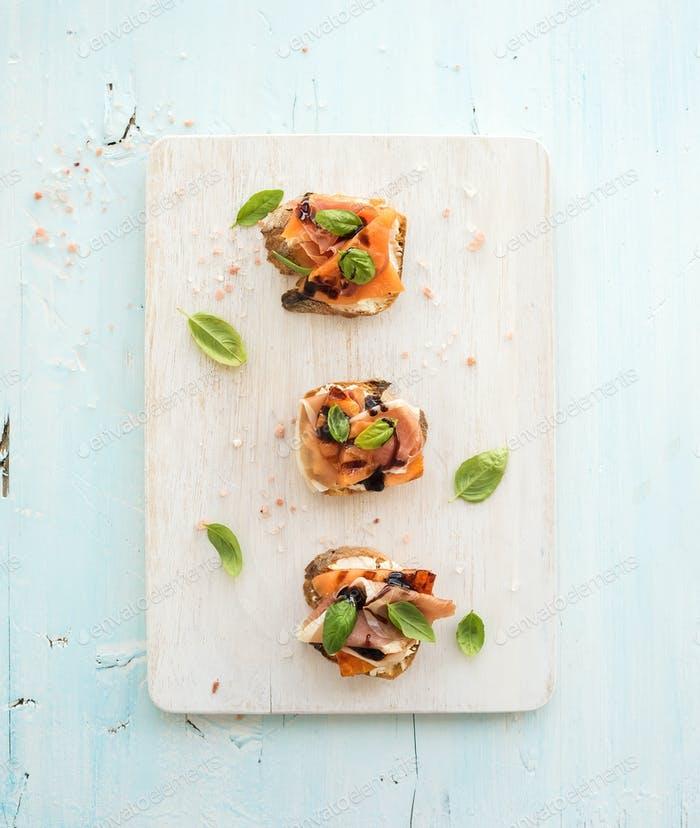 Bruschettas with Prosciutto, roasted melon, soft cheese and basil on wooden serving board