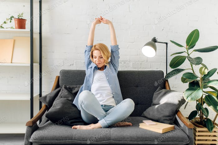 Young woman with book stretch out on cozy couch