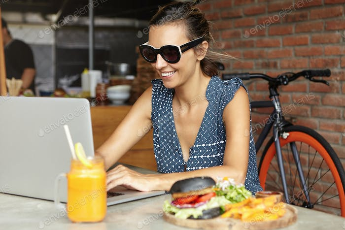 Woman freelancer in stylish sunglasses using laptop pc for remote work, looking at screen with joyfu