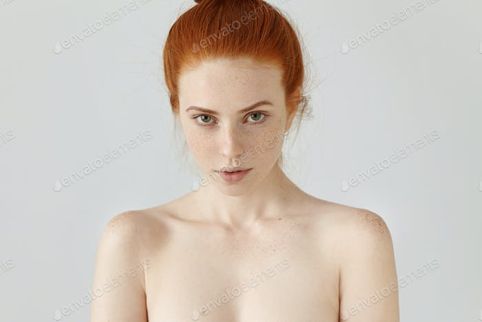 People, beauty and health care. Head and shoulders of extraordinary ginger woman model with freckles