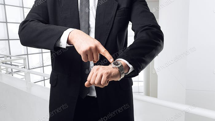 Young businessman point a finger on the watch