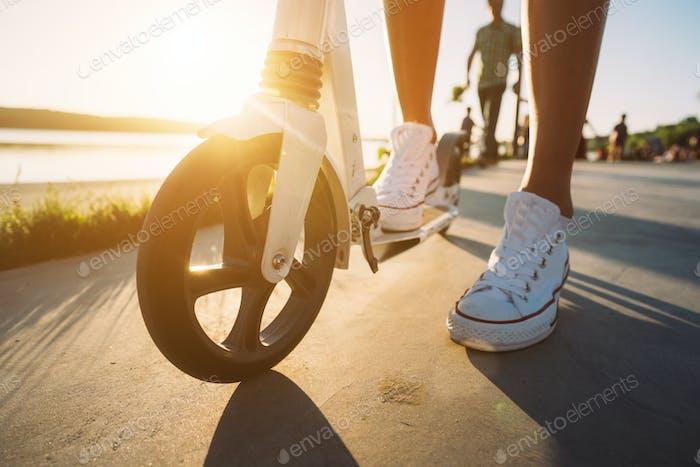 Beine in Jeans und Sneakers auf einem Kick-Scooter über Ansicht