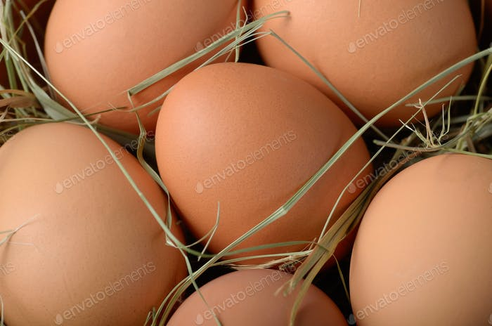 Food background of brown organic eggs in clay bowl