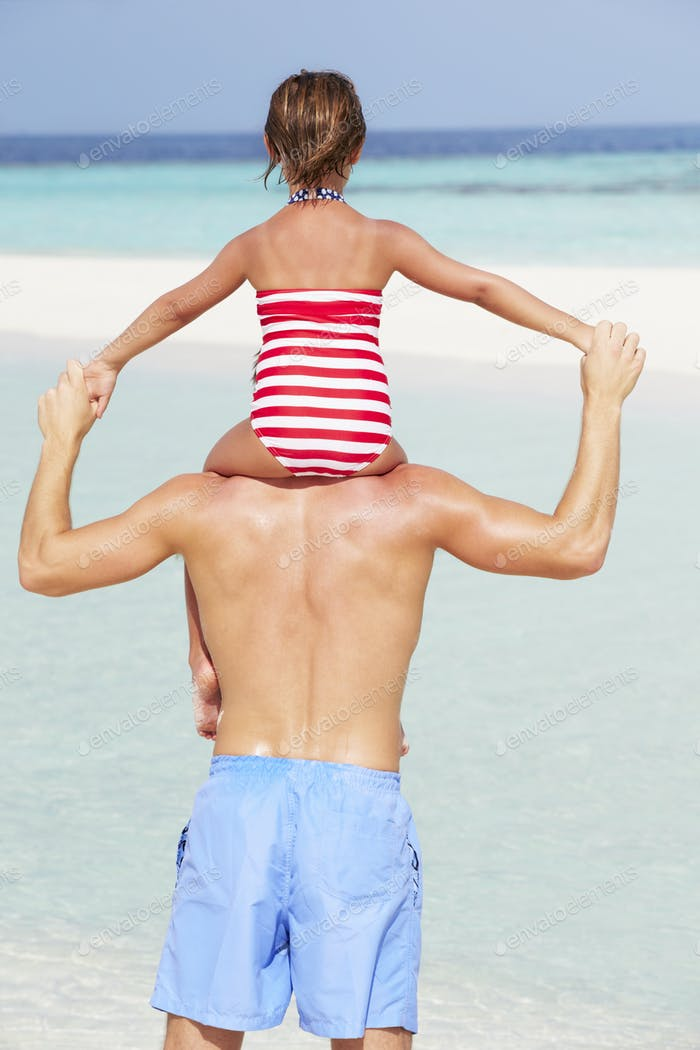 Rear View Of Father Carrying Daughter On Beach Holiday