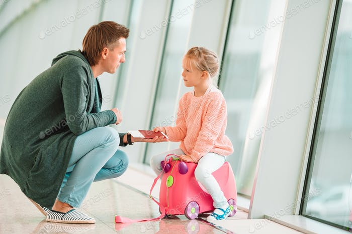 Happy dada and little girl with boarding pass at airport