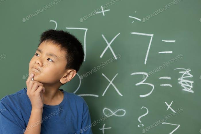 Schoolboy doing math on green chalkboard in a classroom at elementary school