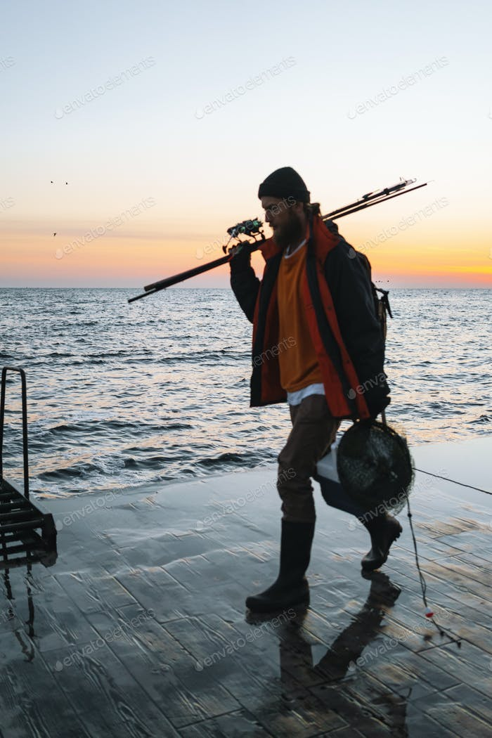 Handsome brutal bearded fisherman wearing coat