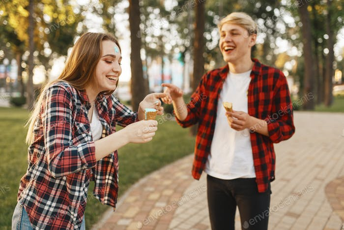Love couple having fun with ice cream in park