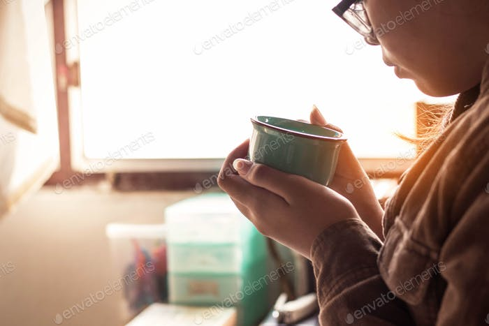 Das Mädchen hielt einen Kaffee bei der Arbeit