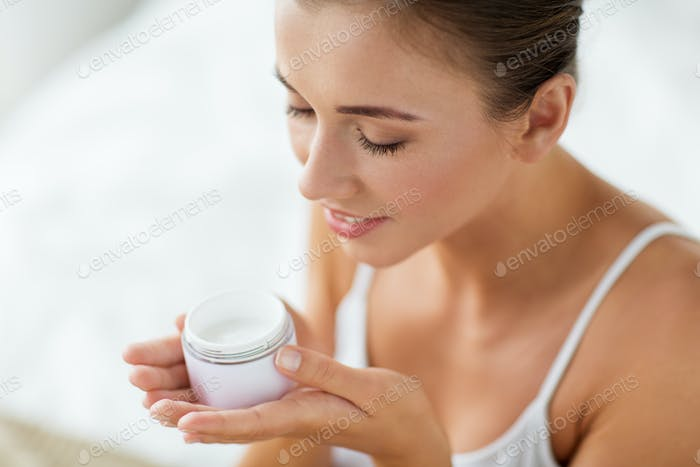 close up of happy woman holding and smelling cream