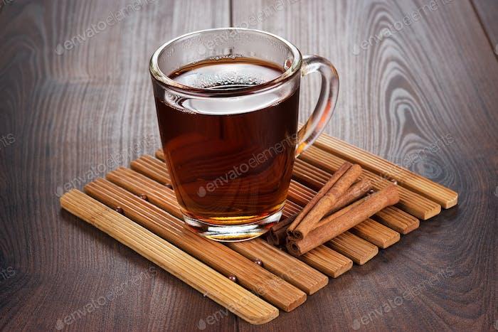 Teetasse mit heißem Tee und Zimtstangen
