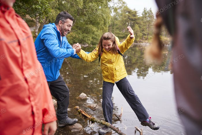 Middle aged father holding his daughters hand while she balances on the shore of a lake