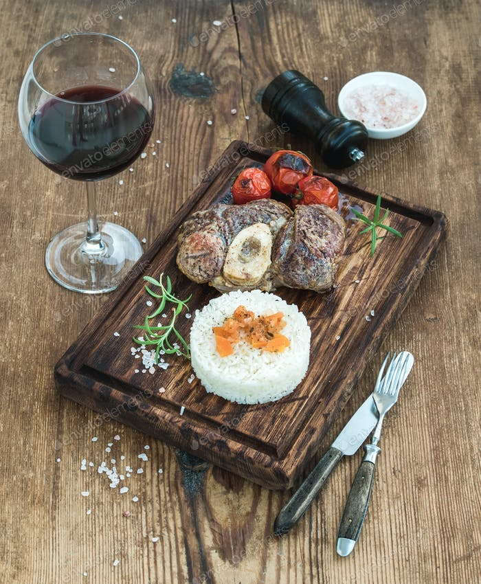 Roast beef Ossobuco with rice, vegetables and glass of wine on serving board