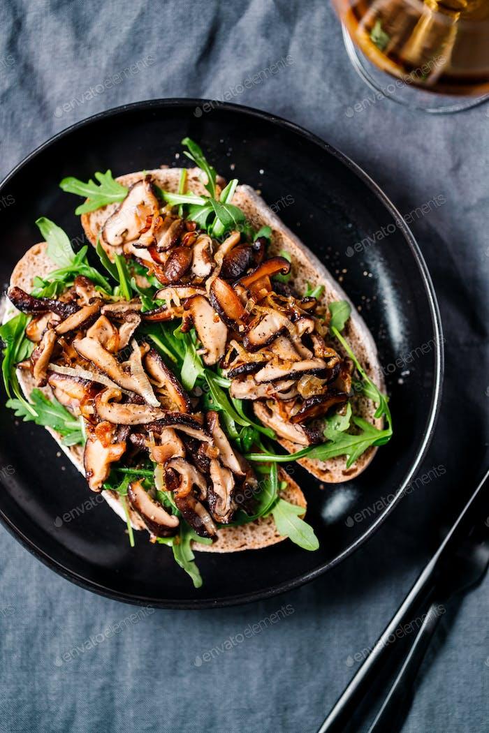 Vista superior de dos sándwiches veganos con rúcula fresca, champiñones shiitake fritos y cebolla chalota.