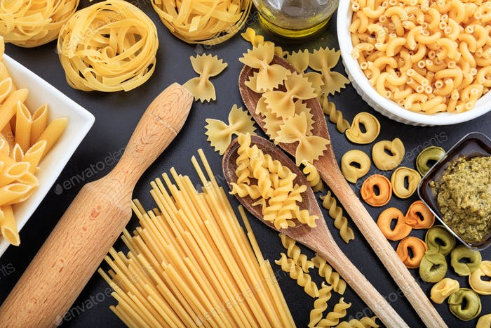 Various shapes of raw pasta on black background