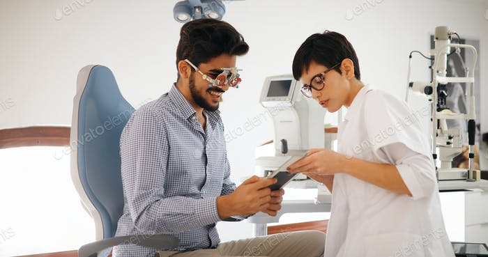 Woman doing eye test with optometrist in eye sight clinic