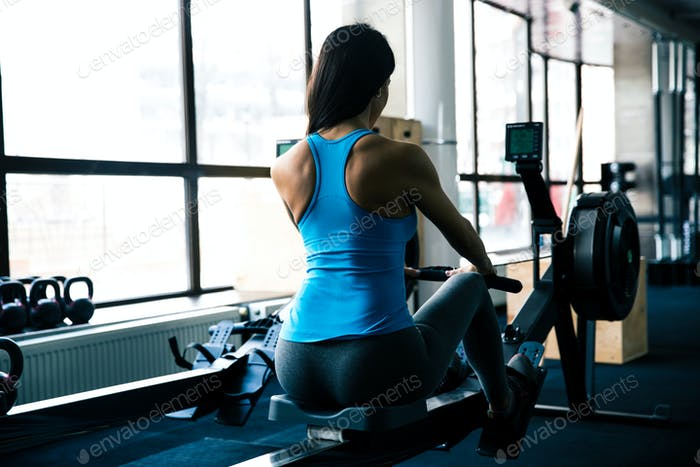 Young woman working out on simulator
