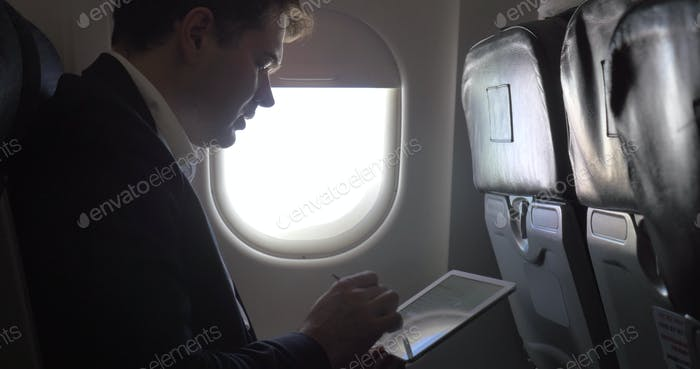 Young businessman working with pad in plane